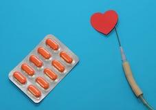 Τα φάρμακα σε ένα μπλε υπόβαθρο για τη θεραπεία των καρδιακών παθήσεων, dropper τη βελόνα και τις ταμπλέτες του πορτοκαλιού χρώμα Στοκ φωτογραφία με δικαίωμα ελεύθερης χρήσης
