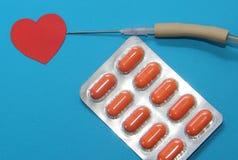 Τα φάρμακα σε ένα μπλε υπόβαθρο για τη θεραπεία των καρδιακών παθήσεων, dropper τη βελόνα και τις ταμπλέτες του πορτοκαλιού χρώμα Στοκ Εικόνες