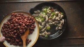 Τα φασόλια διαδίδονται σε ένα τηγανίζοντας τηγάνι με το πιπέρι και το κοτόπουλο βίντεο φιλμ μικρού μήκους