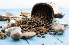 Τα φασόλια καφέ είναι διεσπαρμένα από μια κούπα Καρυκεύματα και σοκολάτα Στοκ Φωτογραφία