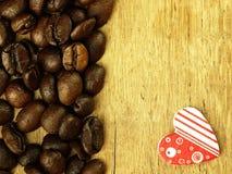 Τα φασόλια καρδιών και καφέ κλείνουν επάνω στον ξύλινο δρύινο πίνακα Στοκ Φωτογραφίες