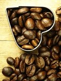 Τα φασόλια καρδιών και καφέ κλείνουν επάνω στον ξύλινο δρύινο πίνακα Στοκ Φωτογραφία