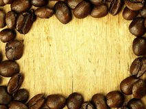Τα φασόλια καφέ κλείνουν επάνω στον ξύλινο δρύινο πίνακα Στοκ εικόνα με δικαίωμα ελεύθερης χρήσης