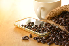 Τα φασόλια καφέ στο σάκο βάζουν στο έξυπνο τηλέφωνο με το φλυτζάνι ο cofee στοκ εικόνες