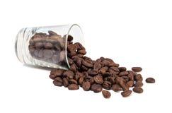 τα φασόλια καφέ χύνουν έξω από τον πυροβολισμό γυαλιού Στοκ Εικόνα