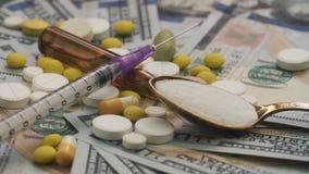 Τα φιαλλίδια, τα χάπια και η σύριγγα είναι σε έναν πίνακα με τα δολάρια Ένα ανθρώπινο χέρι βάζει ένα κουτάλι στα φάρμακα Έννοια ν φιλμ μικρού μήκους