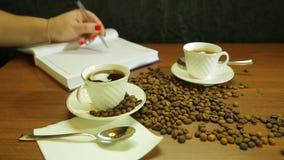 Τα φλυτζάνια του ισχυρού καφέ, μιας διασποράς των φασολιών καφέ στον πίνακα και μιας γυναίκας γράφουν σε ένα ημερολόγιο απόθεμα βίντεο