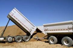 Τα φορτηγά ξεφορτώνουν το αμμοχάλικο στο εργοτάξιο οικοδομής Στοκ φωτογραφία με δικαίωμα ελεύθερης χρήσης