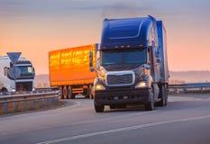 τα φορτηγά πηγαίνουν στην εθνική οδό στο ηλιοβασίλεμα Στοκ Φωτογραφία