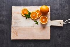 Τα φρέσκα εσπεριδοειδή, οι πορτοκαλιές και μισές πορτοκαλιές φέτες περικοπών στον τέμνοντα πίνακα, σκοτεινό υπόβαθρο πετρών, επίπ Στοκ Εικόνες