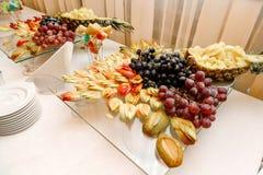 Τα φρέσκα τεμαχισμένα φρούτα σε εορταστικό τα γλυκά επιτραπέζια σταφύλια ανανά επιδορπίων φρούτων Στοκ Εικόνες
