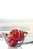 Τα φρέσκα juicy κόκκινα πιπέρια κουδουνιών σε ένα κλουβί σε ένα λευκό παρουσιάζουν σε ένα ηλιόλουστο θερινό υπόβαθρο Στοκ εικόνα με δικαίωμα ελεύθερης χρήσης