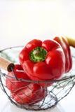Τα φρέσκα juicy κόκκινα πιπέρια κουδουνιών σε ένα κλουβί σε ένα λευκό παρουσιάζουν σε ένα ηλιόλουστο θερινό υπόβαθρο Στοκ Εικόνα
