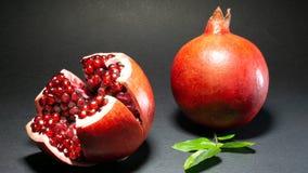 Τα φρούτα ροδιών, ένα πόδι ανοίγουν και μπορείτε να δείτε τα σιτάρια κοντά στο δεύτερο στοκ φωτογραφία