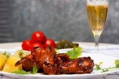 Τα φτερά κοτόπουλου έψησαν στη σχάρα με τις βρασμένες πατάτες και μαρινάρισαν τις ντομάτες Στοκ Εικόνα