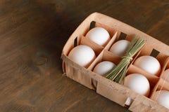 Τα φυσικά οργανικά αυγά κοτόπουλου στην πορτοκαλιά συσκευασία χαρτονιού απομονώνουν στοκ εικόνες