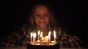Τα φυσώντας κεριά γιορτής γενεθλίων παιδιών στη νύχτα, παιδί γιορτάζουν με το κέικ στο σκοτάδι φιλμ μικρού μήκους