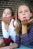 τα φυσώντας κορίτσια φιλούν Στοκ Φωτογραφίες