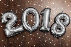 Τα φωτεινά μεταλλικά ασημένια σχήματα το 2018, Χριστούγεννα μπαλονιών, νέο μπαλόνι έτους με ακτινοβολούν αστέρια στο σκοτεινό ξύλ Στοκ φωτογραφίες με δικαίωμα ελεύθερης χρήσης