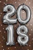 Τα φωτεινά μεταλλικά ασημένια σχήματα το 2018, Χριστούγεννα μπαλονιών, νέο μπαλόνι έτους με ακτινοβολούν αστέρια στο σκοτεινό ξύλ Στοκ εικόνα με δικαίωμα ελεύθερης χρήσης