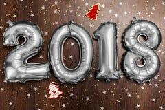 Τα φωτεινά μεταλλικά ασημένια σχήματα το 2018, Χριστούγεννα μπαλονιών, νέο μπαλόνι έτους με ακτινοβολούν αστέρια στο σκοτεινό ξύλ Στοκ Φωτογραφία