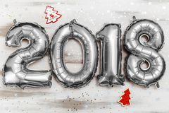 Τα φωτεινά μεταλλικά ασημένια σχήματα το 2018, Χριστούγεννα μπαλονιών, νέο μπαλόνι έτους με ακτινοβολούν αστέρια στον άσπρο ξύλιν Στοκ Φωτογραφία