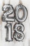 Τα φωτεινά μεταλλικά ασημένια σχήματα το 2018, Χριστούγεννα μπαλονιών, νέο μπαλόνι έτους με ακτινοβολούν αστέρια στον άσπρο ξύλιν Στοκ εικόνες με δικαίωμα ελεύθερης χρήσης