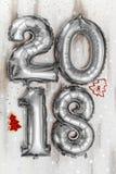Τα φωτεινά μεταλλικά ασημένια σχήματα το 2018, Χριστούγεννα μπαλονιών, νέο μπαλόνι έτους με ακτινοβολούν αστέρια στον άσπρο ξύλιν Στοκ Εικόνες