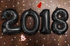 Τα φωτεινά μεταλλικά μαύρα σχήματα το 2018, Χριστούγεννα μπαλονιών, νέο μπαλόνι έτους με ακτινοβολούν αστέρια στο σκοτεινό ξύλινο Στοκ Φωτογραφία