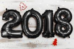 Τα φωτεινά μεταλλικά μαύρα σχήματα το 2018, Χριστούγεννα μπαλονιών, νέο μπαλόνι έτους με ακτινοβολούν αστέρια στον άσπρο ξύλινο π Στοκ Φωτογραφίες