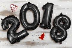 Τα φωτεινά μεταλλικά μαύρα σχήματα το 2018, Χριστούγεννα μπαλονιών, νέο μπαλόνι έτους με ακτινοβολούν αστέρια στον άσπρο ξύλινο π Στοκ Εικόνα