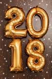 Τα φωτεινά μεταλλικά χρυσά σχήματα το 2018, Χριστούγεννα μπαλονιών, νέο μπαλόνι έτους με ακτινοβολούν αστέρια στο σκοτεινό ξύλινο Στοκ φωτογραφία με δικαίωμα ελεύθερης χρήσης