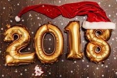Τα φωτεινά μεταλλικά χρυσά σχήματα το 2018, Χριστούγεννα μπαλονιών, νέο μπαλόνι έτους με ακτινοβολούν αστέρια στο σκοτεινό ξύλινο Στοκ Φωτογραφία