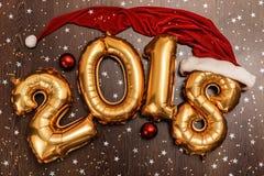 Τα φωτεινά μεταλλικά χρυσά σχήματα το 2018, Χριστούγεννα μπαλονιών, νέο μπαλόνι έτους με ακτινοβολούν αστέρια στο σκοτεινό ξύλινο Στοκ Εικόνες