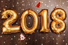 Τα φωτεινά μεταλλικά χρυσά σχήματα το 2018, Χριστούγεννα μπαλονιών, νέο μπαλόνι έτους με ακτινοβολούν αστέρια στο σκοτεινό ξύλινο Στοκ Φωτογραφίες