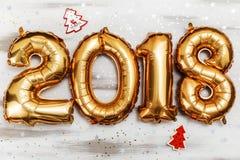Τα φωτεινά μεταλλικά χρυσά σχήματα το 2018, Χριστούγεννα μπαλονιών, νέο μπαλόνι έτους με ακτινοβολούν αστέρια στον άσπρο ξύλινο π Στοκ Εικόνες