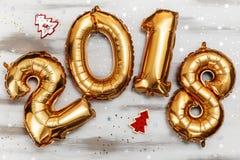 Τα φωτεινά μεταλλικά χρυσά σχήματα το 2018, Χριστούγεννα μπαλονιών, νέο μπαλόνι έτους με ακτινοβολούν αστέρια στον άσπρο ξύλινο π Στοκ Φωτογραφία