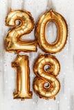 Τα φωτεινά μεταλλικά χρυσά σχήματα το 2018, Χριστούγεννα μπαλονιών, νέο μπαλόνι έτους με ακτινοβολούν αστέρια στον άσπρο ξύλινο π Στοκ φωτογραφίες με δικαίωμα ελεύθερης χρήσης