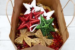 Τα φωτεινά πολύχρωμα παιχνίδια Χριστουγέννων βρίσκονται σε μια τσάντα αγορών εγγράφου Στοκ Φωτογραφία