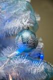 τα φωτεινά Χριστούγεννα σφαιρών ανασκόπησης διακοσμούν το λευκό δέντρων Στοκ Φωτογραφίες
