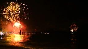 Τα φωτεινά χρυσά πυροτεχνήματα εκρήγνυνται στο νυχτερινό ουρανό επάνω από την επιφάνεια της θάλασσας απόθεμα βίντεο