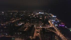 Τα φω'τα νύχτας της μεγάλης πόλης, εναέρια άποψη, αυτοκίνητα κινούνται πέρα από τους δρόμους απόθεμα βίντεο