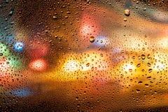 Τα φω'τα πόλεων νύχτας στη βροχή ζωηρόχρωμη το χρωματισμένο υπόβαθρο με τις πτώσεις του νερού Στοκ Φωτογραφία