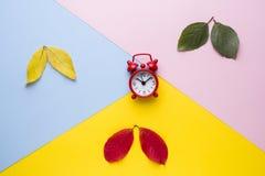 Τα φύλλα είναι πράσινα, κίτρινα και κόκκινα Χρόνος, ξυπνητήρι στο ρολόι Αφαίρεση, η έννοια του φθινοπώρου στοκ φωτογραφία με δικαίωμα ελεύθερης χρήσης