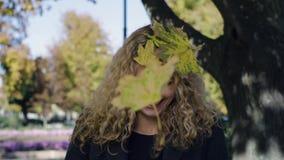 Τα φύλλα σφενδάμου εμπίπτουν στο κεφάλι ενός νέου όμορφου κοριτσιού στο πάρκο σε ένα δέντρο απόθεμα βίντεο