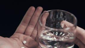 Τα χάπια και το ποτήρι του νερού απομόνωσαν υπό εξέταση το μαύρο άτομο υποβάθρου που παίρνει τα χάπια POV απόθεμα βίντεο