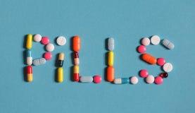 Τα χάπια λέξης είναι ευθυγραμμισμένα με τα χρωματισμένες χάπια και τις ταμπλέτες σε ένα μπλε υπόβαθρο Στοκ φωτογραφίες με δικαίωμα ελεύθερης χρήσης