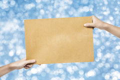 Τα χέρια δίνουν το φάκελο με το μουτζουρωμένο μπλε υπόβαθρο, για προσθέστε το te σας στοκ φωτογραφίες