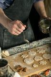 Τα χέρια αρχιμαγείρων χύνουν τη ζάχαρη στην ακατέργαστη διαμορφωμένη ζύμη στοκ φωτογραφίες