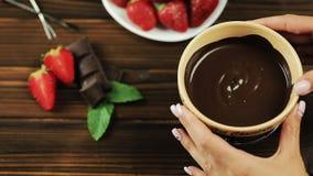 Τα χέρια αρχιμαγείρων ` s βάζουν fondue στον πίνακα Fondue με τις φράουλες σοκολάτας σε ένα ξύλινο υπόβαθρο απόθεμα βίντεο